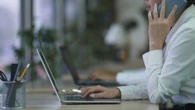 Υπάλληλος τηλεφωνικών κέντρων που έχει τη τηλεφωνική συνομιλία με τον πελάτη, που εργάζεται στο lap-top φιλμ μικρού μήκους