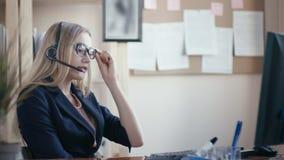 Υπάλληλος τηλεφωνικών κέντρων στην εργασία στο γραφείο Ένα νέο κορίτσι με τα ξανθά μαλλιά με τα γυαλιά που κάθεται σε έναν πίνακα απόθεμα βίντεο