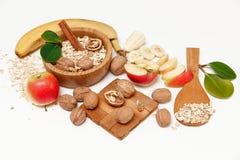 Υπάρχει μπανάνα, Apple, ξύλα καρυδιάς στο ξύλινο πιάτο και τις κυλημένες βρώμες, ξύλινο κουτάλι, Trivet, με τα πράσινα φύλλα, το  Στοκ Εικόνες