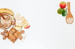 Υπάρχει μπανάνα, Apple, πορτοκάλι με τα ξύλα καρυδιάς στο ξύλινο πιάτο και τις κυλημένες βρώμες, ξύλινο κουτάλι, Trivet, με τα πρ Στοκ εικόνα με δικαίωμα ελεύθερης χρήσης