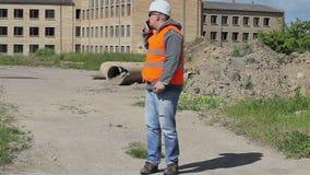Υπάλληλοι οικοδόμησης που μιλούν κοντά στο ατελές κτήριο απόθεμα βίντεο