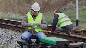 Υπάλληλοι σιδηροδρόμων που εργάζονται στο σιδηρόδρομο φιλμ μικρού μήκους