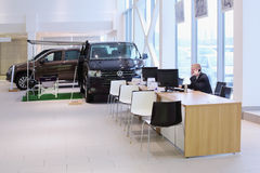 Υπάλληλος εμποριών αυτοκινήτων και δύο αυτοκίνητα Στοκ εικόνες με δικαίωμα ελεύθερης χρήσης