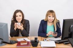 Υπάλληλος δύο γραφείων που συμμετέχεται στην προσωπική επιχείρηση στα κινητά τηλέφωνα στο γραφείο του Στοκ Εικόνες