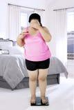 Υπέρβαρη γυναίκα με την κλίμακα στην κρεβατοκάμαρα Στοκ φωτογραφία με δικαίωμα ελεύθερης χρήσης