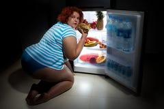 Υπέρβαρη γυναίκα με το ψυγείο Στοκ Φωτογραφίες