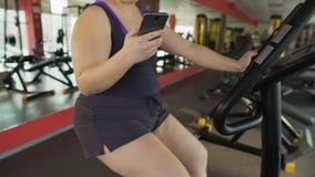 Υπέρβαρη γυναίκα που οδηγά αργά το στάσιμο ποδήλατο και που κουβεντιάζει στο κινητό τηλέφωνο απόθεμα βίντεο