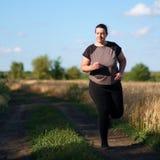 Υπέρβαρη γυναίκα που τρέχει στην επαρχία στοκ εικόνα