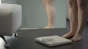 Υπέρβαρη θηλυκή διστακτικότητα πρίν περπατεί στις κλίμακες για να ελέγξει το βάρος, φόβος απόθεμα βίντεο