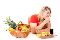 Υπέρβαρη νέα γυναίκα που επιλέγει το άχρηστο φαγητό στοκ φωτογραφία