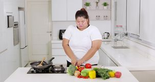Υπέρβαρη νέα γυναίκα που προετοιμάζει τα λαχανικά φιλμ μικρού μήκους