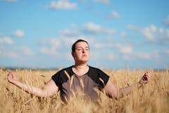 Υπέρβαρη meditating συνεδρίαση γυναικών στον τομέα στοκ φωτογραφία με δικαίωμα ελεύθερης χρήσης