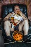 Υπέρβαρο άτομο που τρώει και που προσέχει τη TV στοκ εικόνες