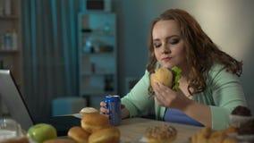 Υπέρβαρο κορίτσι που τρώει burger και που πίνει τη σόδα προσέχοντας τον κινηματογράφο στο lap-top απόθεμα βίντεο