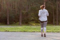 Υπέρβαρο πίσω τρέξιμο γυναικών όμορφη απώλεια έννοιας κοιλιών πέρα από τη λευκή γυναίκα βάρους Στοκ φωτογραφία με δικαίωμα ελεύθερης χρήσης