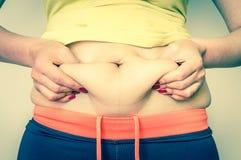 Υπέρβαρο σώμα γυναικών με τα χέρια σχετικά με το λίπος κοιλιών Στοκ Εικόνα