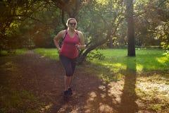 Υπέρβαρο τρέξιμο γυναικών όμορφη απώλεια έννοιας κοιλιών πέρα από τη λευκή γυναίκα βάρους Στοκ Εικόνα