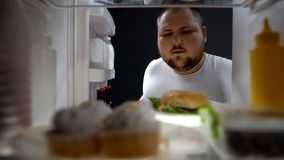 Υπέρβαρο ψυγείο ανοίγματος νεαρών άνδρων για να πάρει τη νύχτα μεγάλο burger, θερμίδες στοκ εικόνα