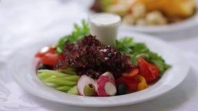 Υπέροχα διακοσμημένες φρέσκες σαλάτες σκηνή Υπέροχα διακοσμημένο πιάτο με τη φυτική σαλάτα στο εστιατόριο φιλμ μικρού μήκους