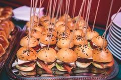 Υπέροχα διακοσμημένος εξυπηρετώντας τον πίνακα συμποσίου με τα διαφορετικά σάντουιτς burgers χάμπουργκερ σε ένα πιάτο στα εταιρικ στοκ εικόνες
