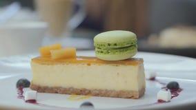 Υπέροχα εξυπηρετούμενο νόστιμο cheesecake με το μάγκο και τα μούρα και πράσινο macaron στο εστιατόριο o φιλμ μικρού μήκους