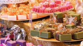 Υπέροχα συσκευασμένα ζωηρόχρωμα ανάμεικτα χειροποίητα σαπούνια στη διάφορα μορφή και το μέγεθος ραφιών στην αγορά Χριστουγέννων απόθεμα βίντεο