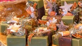 Υπέροχα συσκευασμένα πράσινα ανάμεικτα χειροποίητα σαπούνια στη διάφορα μορφή και το μέγεθος ραφιών στην αγορά Χριστουγέννων απόθεμα βίντεο
