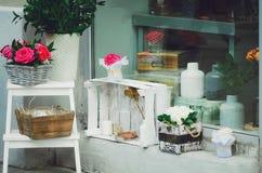 Υπέροχα σχεδιασμένος storefront, λουλούδια και σκάφη γυαλιού κόκκινος τρύγος ύφους κρίνων απεικόνισης στοκ εικόνες