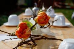 Υπέροχα τοποθετημένος ξύλινος πίνακας με τα λουλούδια και το άσπρο σύνολο καφέ στοκ εικόνες