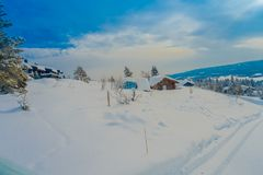 Υπαίθρια άποψη του όμορφου τοπίου των ξύλινων κτηρίων με τα δέντρα πεύκων που καλύπτονται με το χιόνι και τον πάγο στο δάσος κατά Στοκ Εικόνες