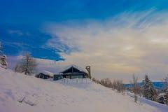 Υπαίθρια άποψη του όμορφου τοπίου των ξύλινων κτηρίων με τα δέντρα πεύκων που καλύπτονται με το χιόνι και τον πάγο στο δάσος κατά Στοκ Φωτογραφίες