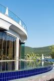Υπαίθρια λίμνη ξενοδοχείων πολυτελείας με τους φοίνικες και θάλασσα στο υπόβαθρο Στοκ εικόνες με δικαίωμα ελεύθερης χρήσης