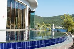 Υπαίθρια λίμνη ξενοδοχείων πολυτελείας με τους φοίνικες και θάλασσα στο υπόβαθρο Στοκ φωτογραφία με δικαίωμα ελεύθερης χρήσης