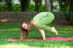 υπαίθρια γιόγκα Ευτυχής γυναίκα που κάνει τις ασκήσεις γιόγκας, meditate στο πάρκο Όμορφη γιόγκα άσκησης γυναικών στη χλόη στοκ φωτογραφία με δικαίωμα ελεύθερης χρήσης