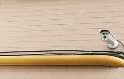 Υπαίθρια κάμερα παρακολούθησης σε ένα τούβλο χλωμό - ρόδινος τοίχος στοκ εικόνα