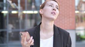 Υπαίθρια νέα επιχειρηματίας που ανατρέπεται από την απώλεια χρησιμοποιώντας Smartphone απόθεμα βίντεο