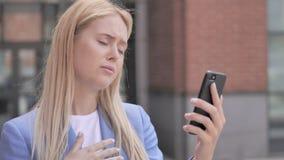 Υπαίθρια νέα επιχειρηματίας που αντιδρά στην απώλεια σε Smartphone φιλμ μικρού μήκους