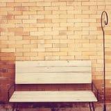 Υπαίθρια ξύλινη καρέκλα στο τουβλότοιχο στοκ φωτογραφία με δικαίωμα ελεύθερης χρήσης