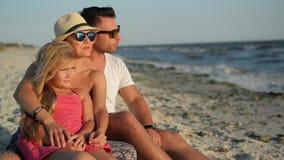 Υπαίθρια πορτρέτο της ευτυχούς οικογένειας με μια κόρη στη συνεδρίαση διακοπών στην παραλία Χαμογελώντας γονείς στα γυαλιά ηλίου  φιλμ μικρού μήκους