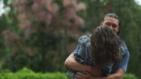 Υπαίθρια πορτρέτο του ευτυχούς ζεύγους στο πάρκο πόλεων Το όμορφο άτομο στροβιλίζεται τη φίλη της σε δικοί του παραδίδει τη βροχή απόθεμα βίντεο