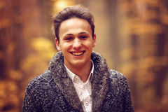 Υπαίθρια πορτρέτο του ευτυχούς νεαρού άνδρα που στέκεται στο πάρκο φθινοπώρου Στοκ Εικόνα