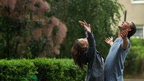 Υπαίθρια πορτρέτο δύο όμορφων εραστών που απολαμβάνουν τη θερμή θερινή βροχή Γυναίκα Brunette και ο φίλος της στον υγρό ιματισμό απόθεμα βίντεο