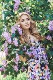 Υπαίθρια όμορφη νέα γυναίκα μόδας που περιβάλλεται μέχρι το ιώδες καλοκαίρι λουλουδιών Ιώδης θάμνος ανθών άνοιξη Πορτρέτο ενός κο Στοκ εικόνες με δικαίωμα ελεύθερης χρήσης