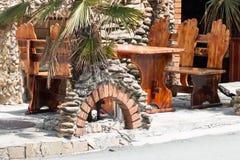 Υπαίθριοι ξύλινοι πάγκος και πίνακας στο εστιατόριο Στοκ εικόνες με δικαίωμα ελεύθερης χρήσης