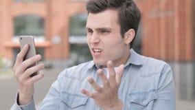 Υπαίθριος νεαρός άνδρας που ανατρέπεται από την απώλεια στο smartphone απόθεμα βίντεο