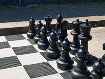 Υπαίθριος πίνακας σκακιού οδών με τα μεγάλα μαύρα πλαστικά κομμάτια στοκ φωτογραφία με δικαίωμα ελεύθερης χρήσης