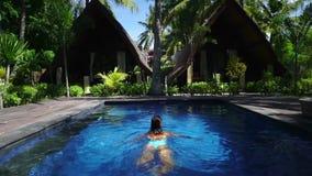 Υπαίθριος πυροβολισμός της γυναίκας που κολυμπά στις όμορφες ζούγκλες πισινών απόθεμα βίντεο