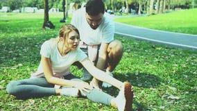 Υπαίθριος πυροβολισμός της νέας ερωτευμένης άσκησης ζευγών στον τομέα χλόης φιλμ μικρού μήκους
