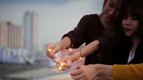 Υπαίθριος πυροβολισμός των νέων στο κόμμα στεγών Η ευτυχής ομάδα φίλων κοριτσιών της Ασίας απολαμβάνει και παίζει sparkler στο το απόθεμα βίντεο