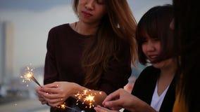 Υπαίθριος πυροβολισμός των νέων στο κόμμα στεγών Η ευτυχής ομάδα φίλων κοριτσιών της Ασίας απολαμβάνει και παίζει sparkler στο το φιλμ μικρού μήκους